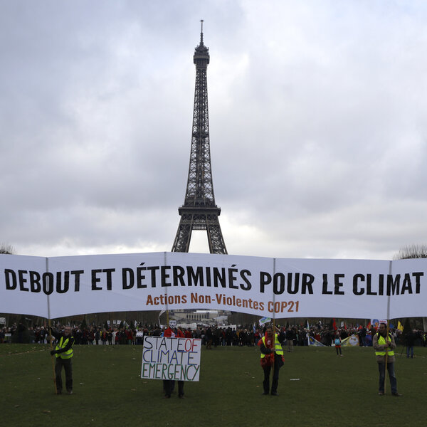 "Activists hold a banner reading ""standing and decided for climate"" during a demonstration near the Eiffel Tower in Paris on Dec. 12, 2015, during the United Nations Climate Change Conference."