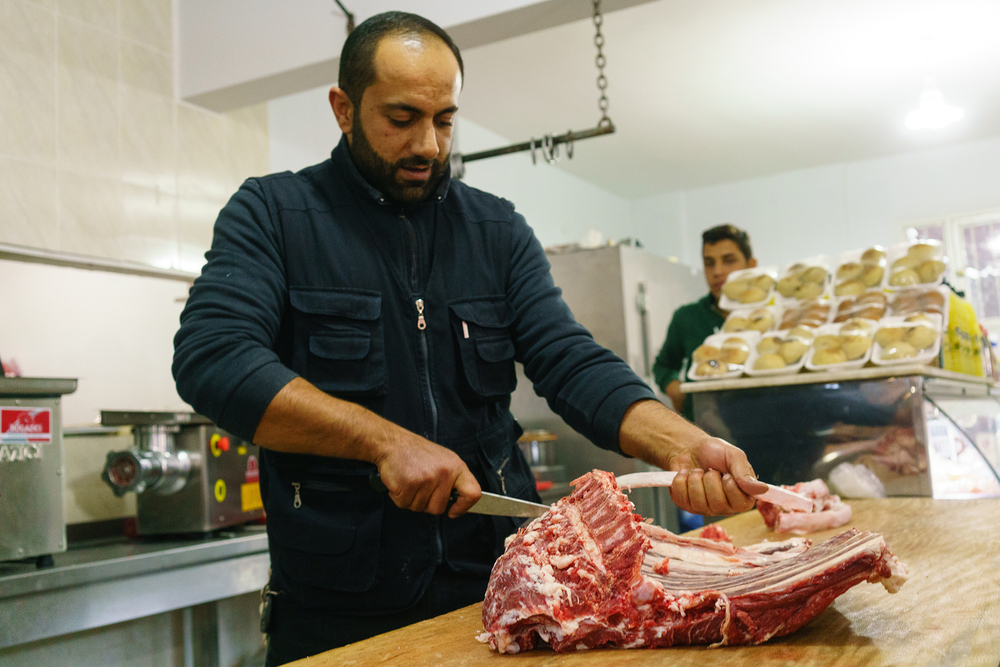 Abu Mohammed, the owner of Sultan Kesap restaurant in the Southern Turkish city of Reyhanli, debones a lamb for meat. His butcher shop/eatery provides his displaced countrymen with culinary reminders of home during better days.