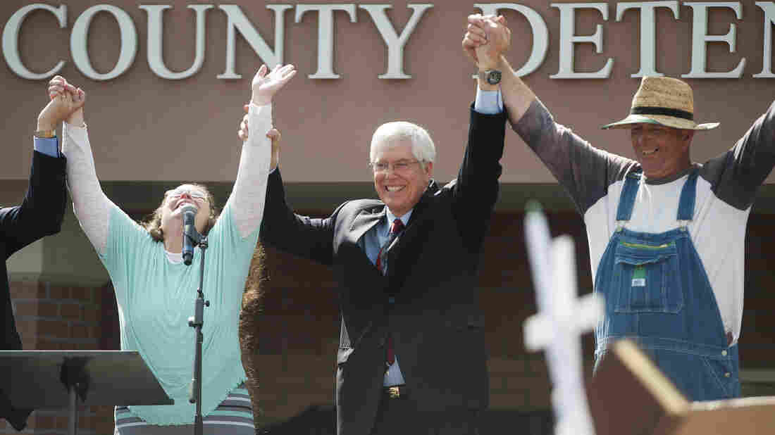 Kim Davis (left) holds her hands in the air with attorney Mat Staver (center) and her husband, Joe Davis, after she was released from jail. She was jailed for her refusal to grant same-sex-marriage licenses.