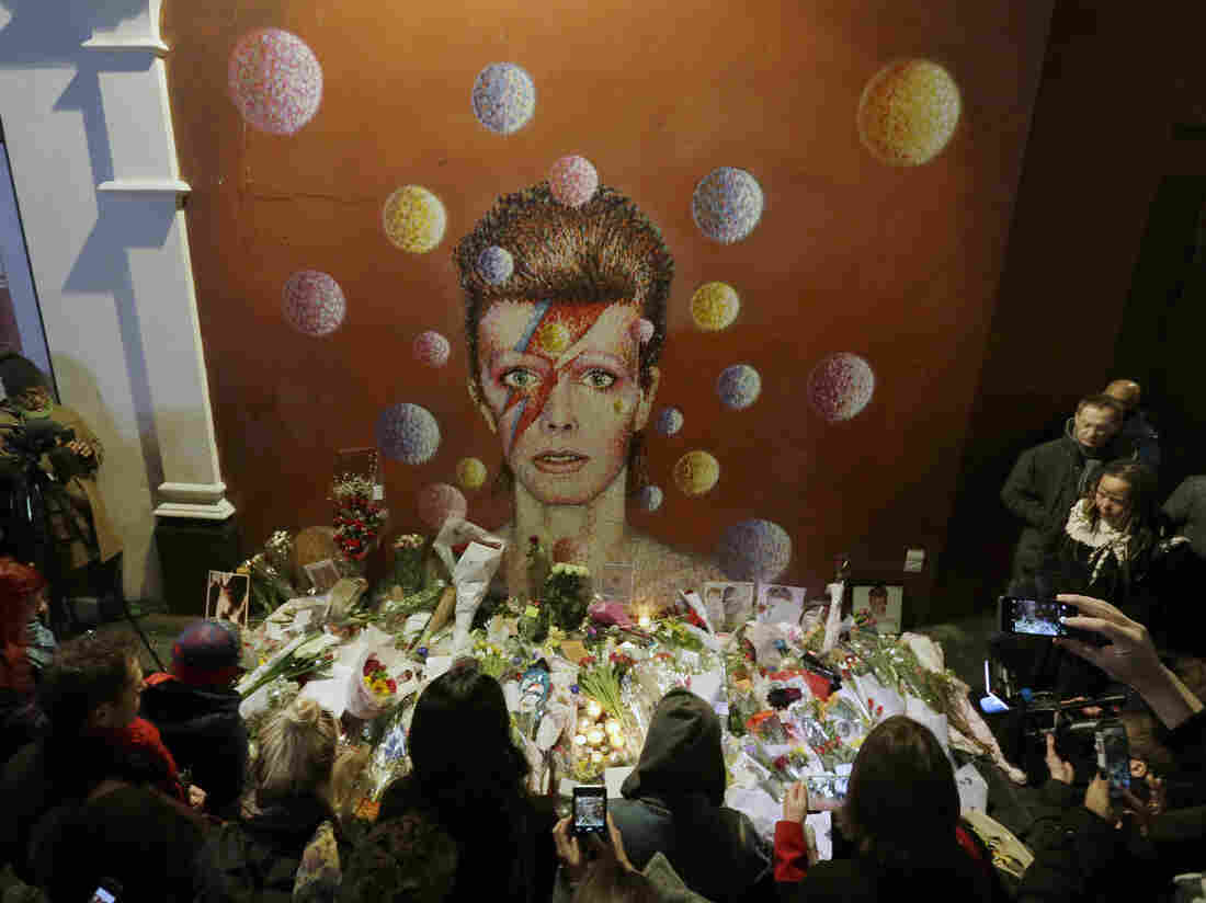 People pay tribute to British singer David Bowie in front of a mural by artist Jimmy C in London on Jan. 11.