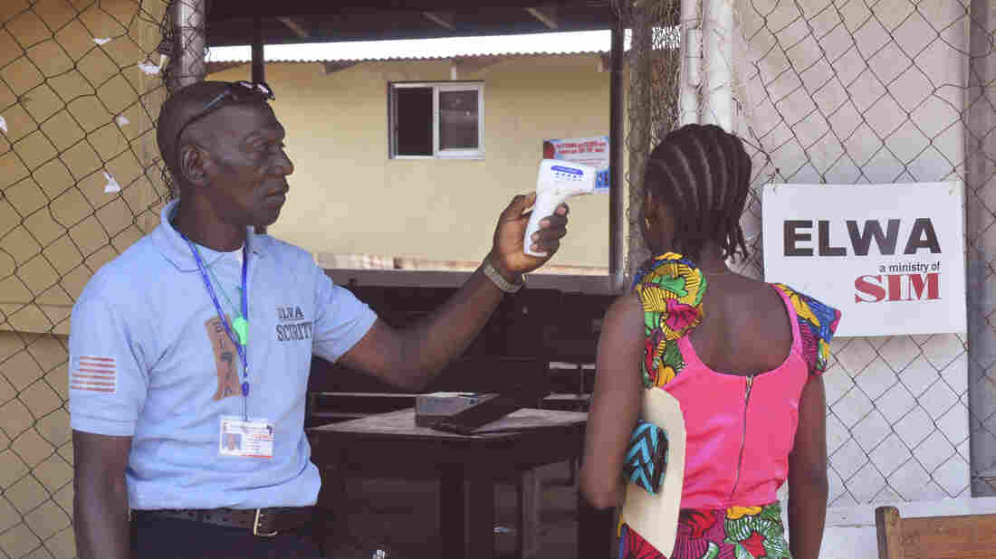 A unidentified family member (right) of a 10-year-old boy that contracted Ebola has her temperature measured by a health worker outside an Ebola clinic on the outskirts of Monrovia, Liberia, on Nov. 20. Liberia, Guinea and Sierra Leone have now gone 42 days without a single reported case of Ebola.