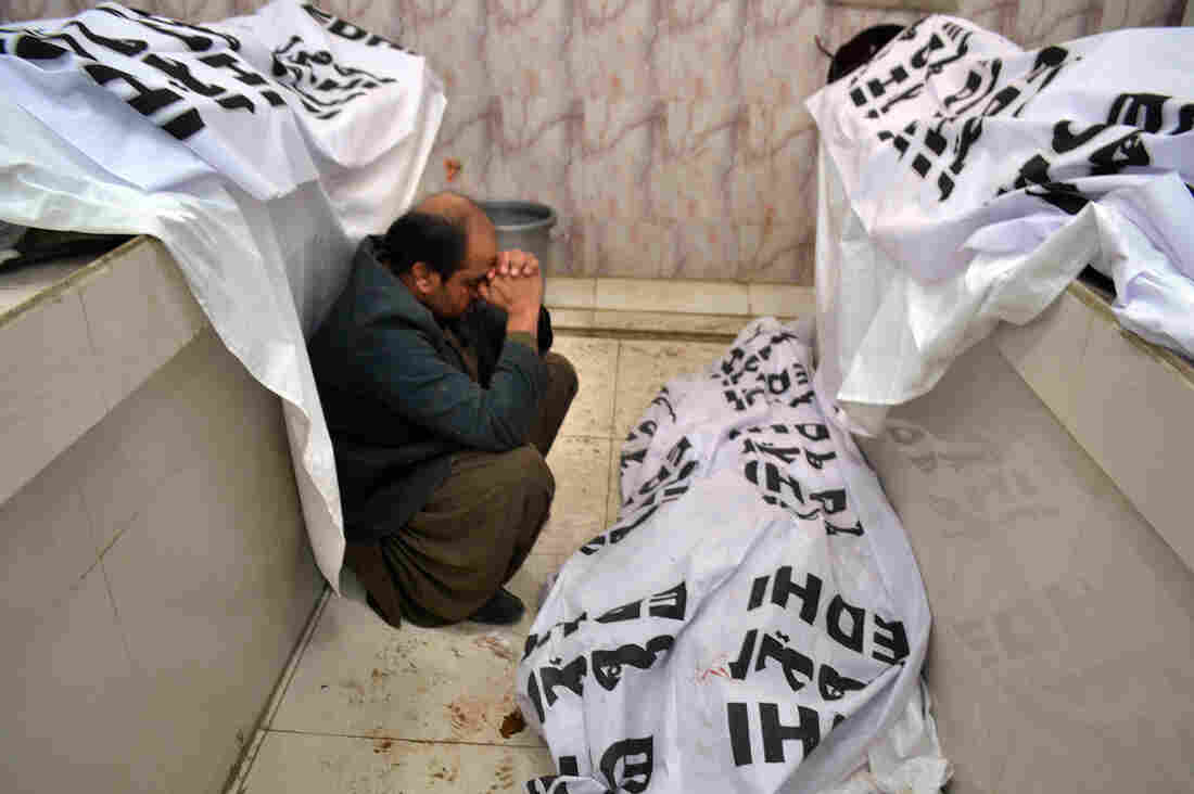 A Pakistani mourner sits alongside bodies of blast victims following a bombing near a polio vaccination center at a hospital in Quetta.