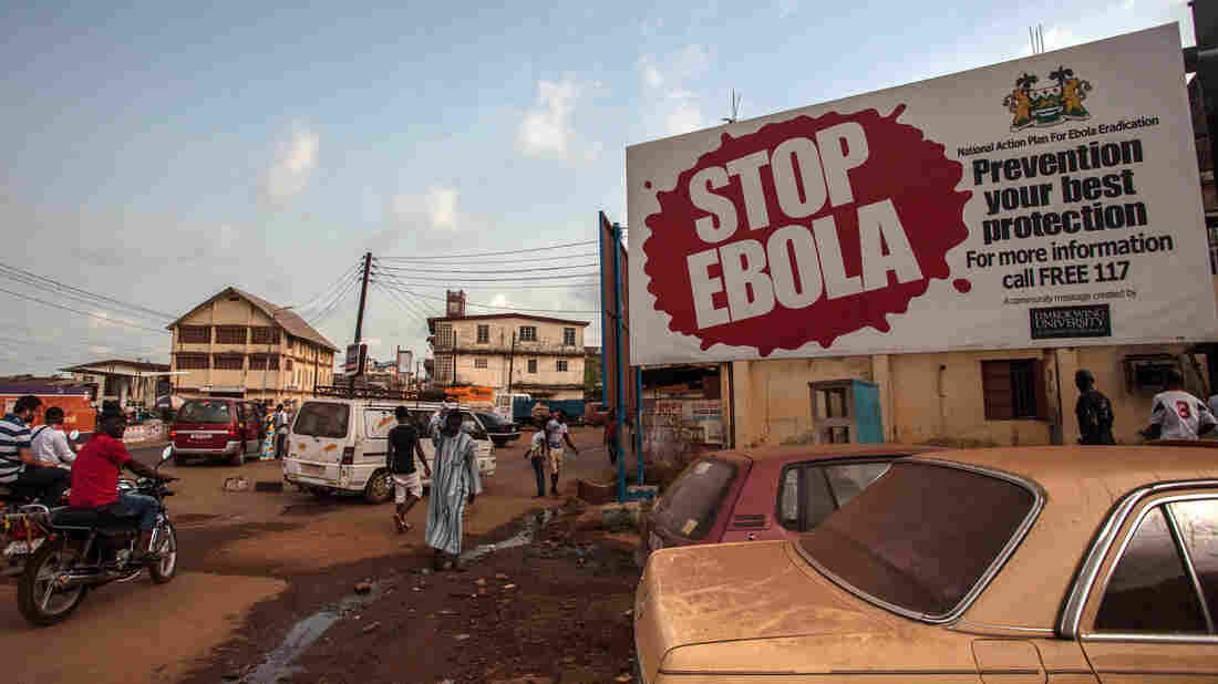"""A corpse has tested positive for the Ebola virus in Sierra Leone, a day after world health officials declared West Africa free of the disease. On Friday, people pass a banner reading """"STOP EBOLA"""" — part of Sierra Leone's health campaign — in the city of Freetown."""