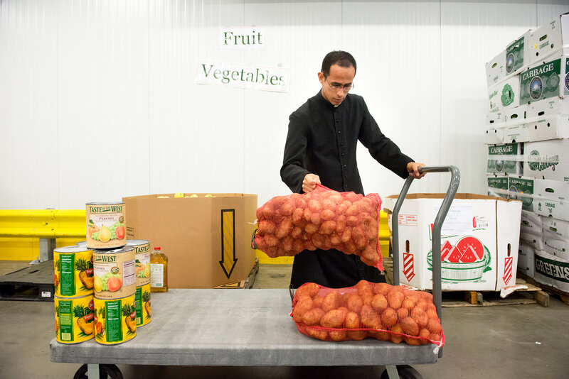 Brother William Valle of the Institute of the Incarnate Word in Chillum, Md., loads potatoes onto his cart at the Capitol Area Food Bank, in Washington, D.C. A new government initiative seeks to engage faith-based groups on food waste — for instance, by using their existing relationships with food banks to redirect excess food to the hungry. (Sarah L. Voisin/The Washington Post via Getty Images)