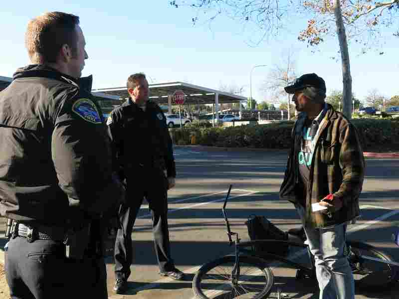 Officers Colin Lewis and Brad Smith (center) on patrol near a park in Huntington Beach, Calif. The area has seen a sharp increase in homelessness and petty thefts, which the officers blame on Proposition 47. But the law's supporters say other California cities have seen declines in property crime.