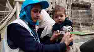 Dr. Rajia Sharhan, UNICEF Nutrition Specialist, takes a child's mid-upper arm circumference in Madaya, Syria, on Thursday. The city was under siege by government forces and didn't receive aid for months. Dozens of people have died of malnutrition.