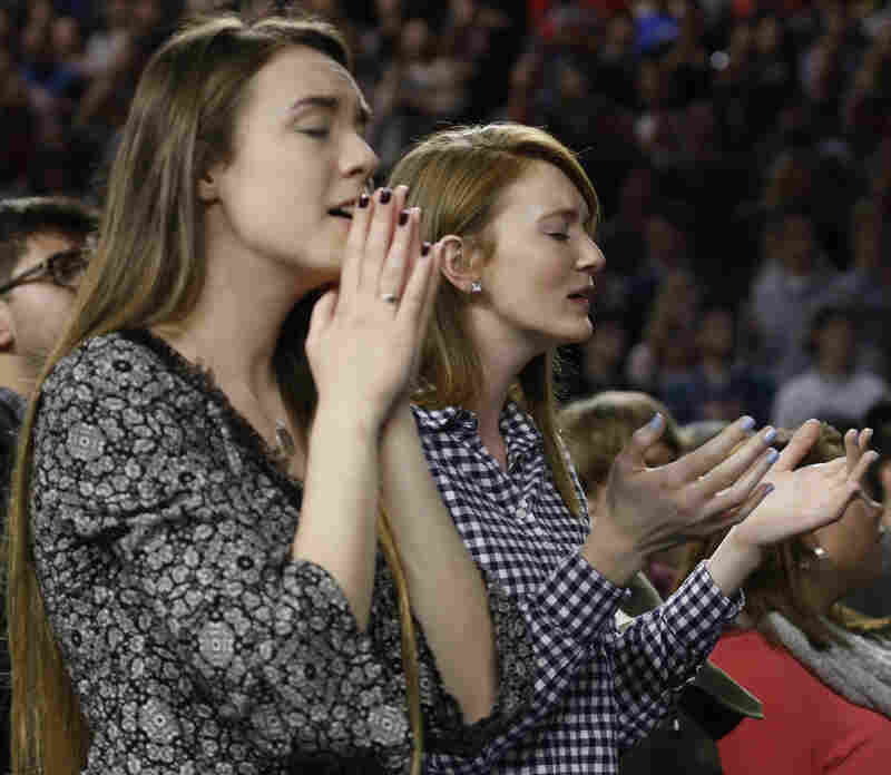 Students at Liberty University sing and pray as they wait for a speech by Donald Trump.
