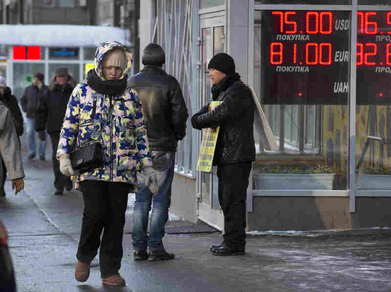 Pedestrians in Moscow walked past a sign showing a drop in the value of the ruble last week. Russia is one of the oil-producing nations cited by the IMF as facing lower-than-expected growth.