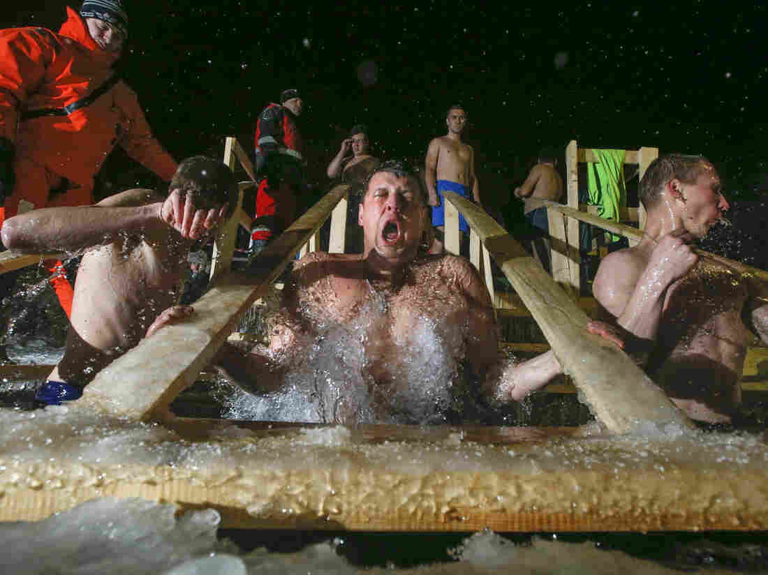 Russian Orthodox believers swim in frigid water at a pond outside St. Petersburg in the wee hours of Tuesday morning. Warmly dressed emergency medical technicians stand by in case anyone is overcome by the cold.