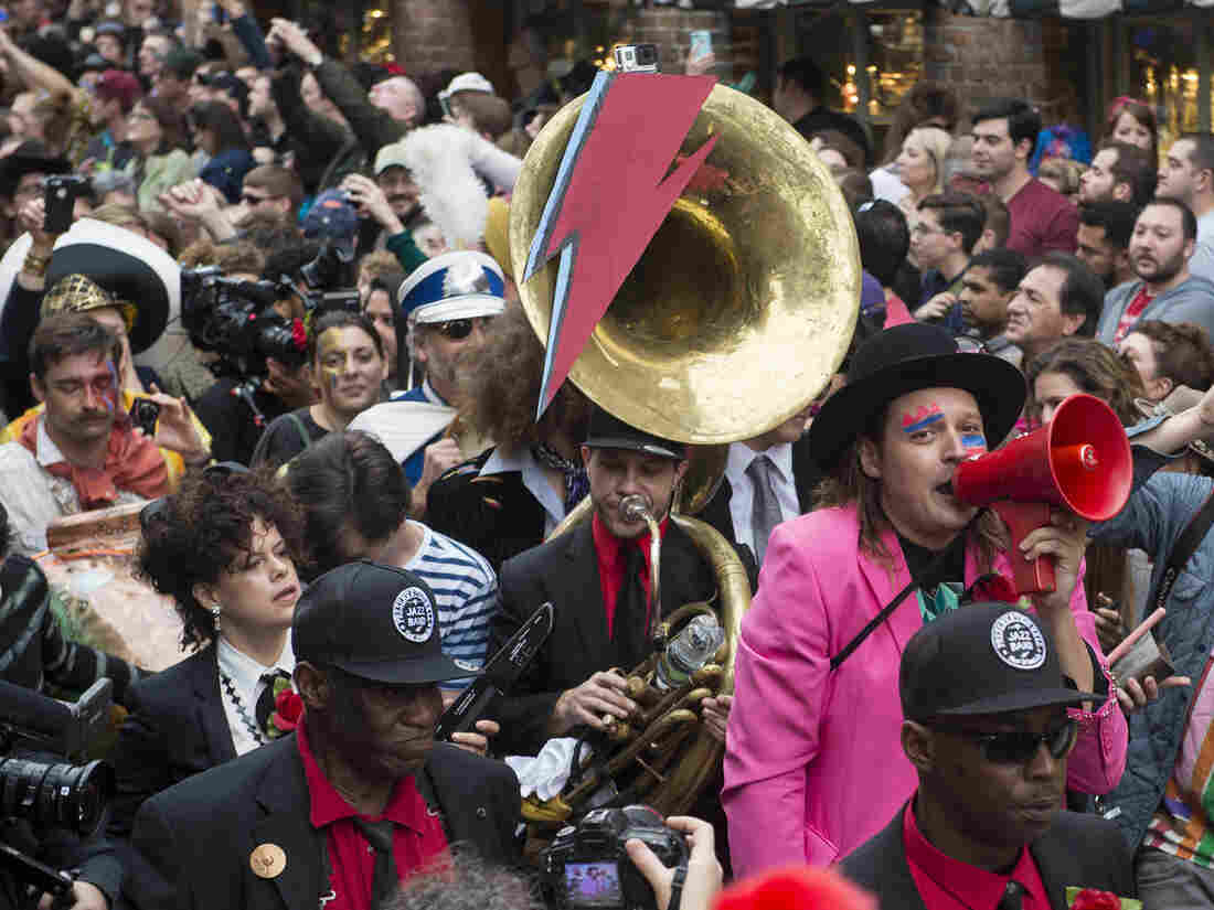 Win Butler (with red megaphone) and Regine Chassagne (lower left, with keytar) of Arcade Fire lead a parade through New Orleans' French Quarter with members of the Preservation Hall Jazz Band in honor of David Bowie.