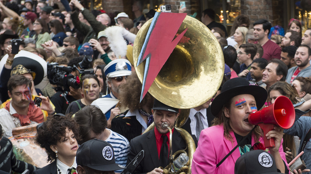 Win Butler (with red megaphone) and Regine Chassagne (lower left, with keytar) of Arcade Fire lead a parade through New Orleans' French Quarter with members of the Preservation Hall Jazz Band in honor of David Bowie. (Erika Goldring for NPR)