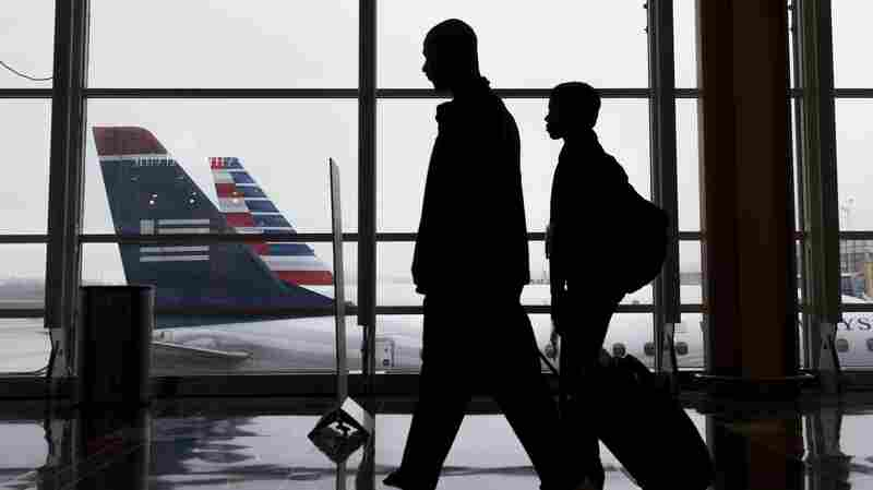 Passengers walk through the terminal as they head to their flights at Reagan National Airport in Arlington, Va., on Dec. 23, 2015.
