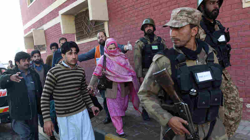 Pakistani soldiers rescue people from Bacha Khan University after an attack by militants in Charsadda on Wednesday. At least 20 people died in an armed assault on the university in northwest Pakistan.