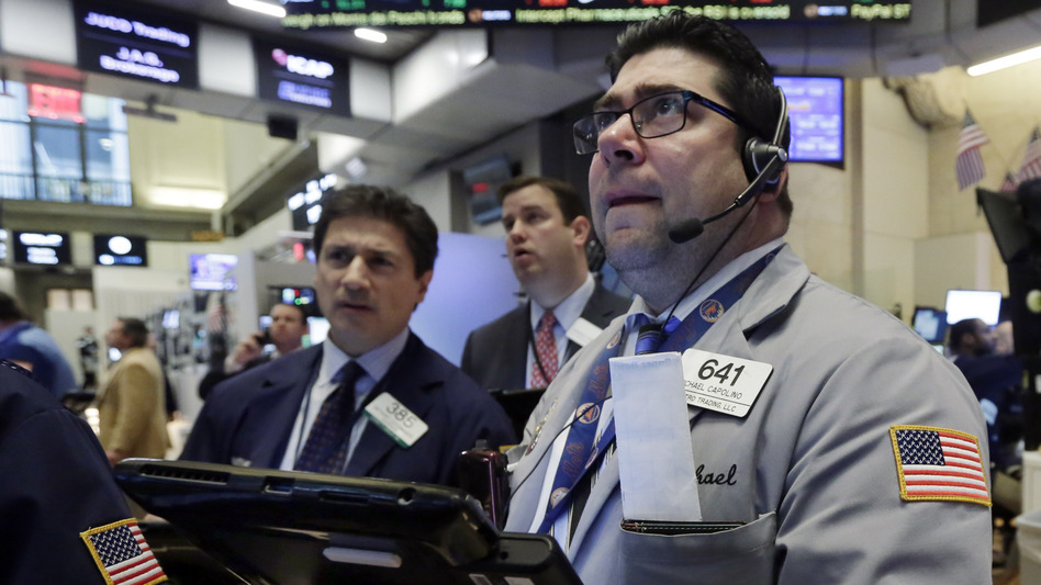 Trader Michael Capolino (right) watches prices on the floor of the New York Stock Exchange Wednesday. Stocks endured another bloodbath, and oil fell below $27 a barrel. (Richard Drew/AP)