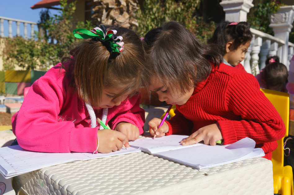 Two Syrian girls color at Bayti orphanage in Reyhanli, Turkey, just across the border from Syria. Many young Syrian refugees have lost one or both parents, but space is limited at orphanages in the city.