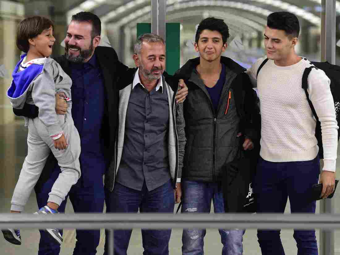 Syrian refugee Osama Abdul Mohsen (middle) is greeted as he arrives in Madrid in September with sons Zaid (far left) and Mohammad (second from right). Abdul Mohsen was tripped by a camerawoman as he scrambled across a field on the Serbia-Hungary border last fall. That incident was seen worldwide and resulted in a job offer from Miguel Ángel Galán (second from left) coaching soccer in Spain.