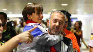 Osama Abdul Mohsen holds his son Zaid as they arrive at the Barcelona train station on Sept. 16, 2015.