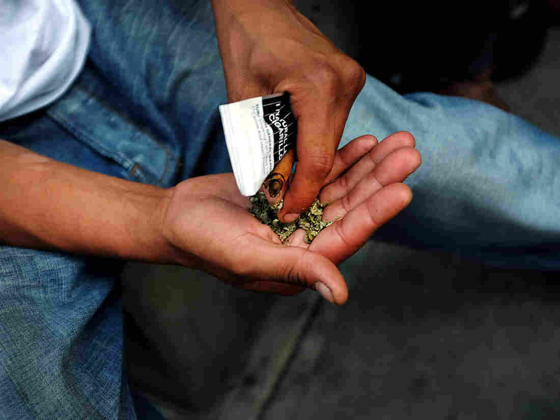 A man prepares to smoke synthetic marijuana on a street in East Harlem in New York City.