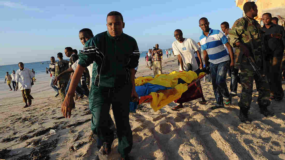 People carry away a body from Lido beach in Mogadishu, Somalia, after an attack on a beachfront restaurant.
