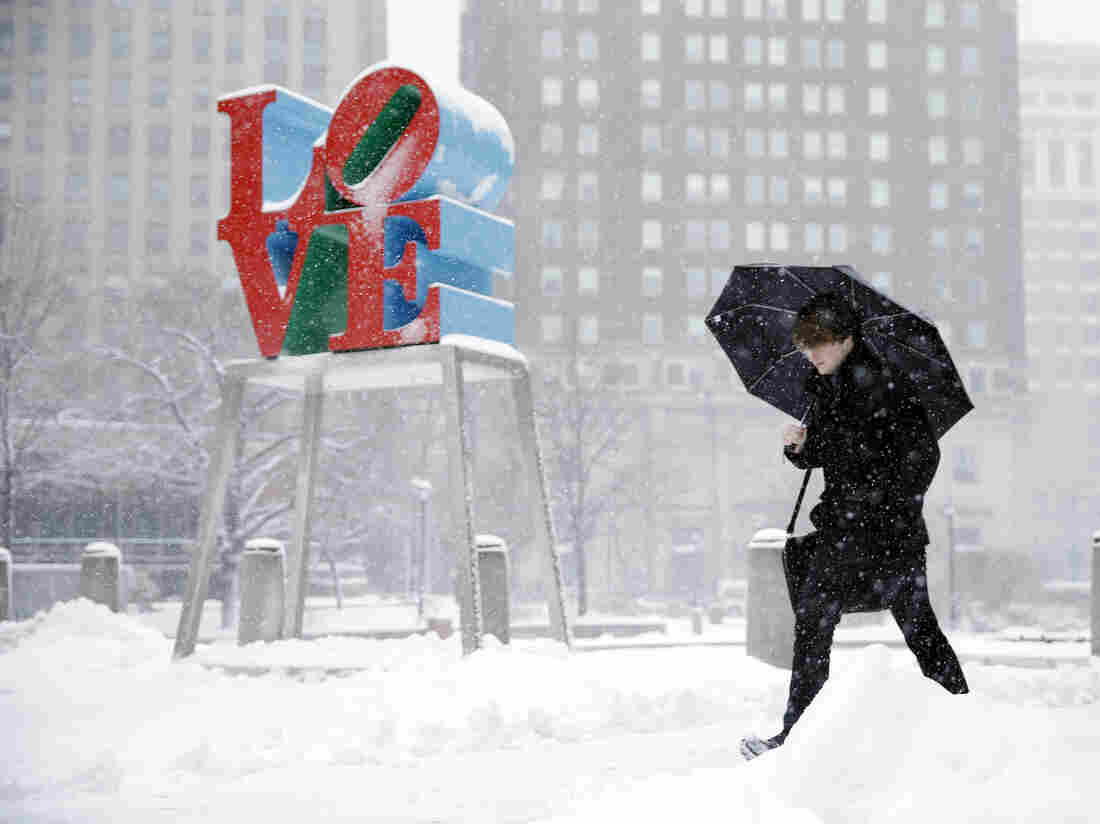 """A man walks through the snow during a winter storm at at JFK Plaza, commonly known as Love Park, in Philadelphia. Why are such storms linked with an uptick in births? Researcher Richard Evans has a theory: """"If the lights go out and there's no TV, it kind of sets the table for romance."""""""