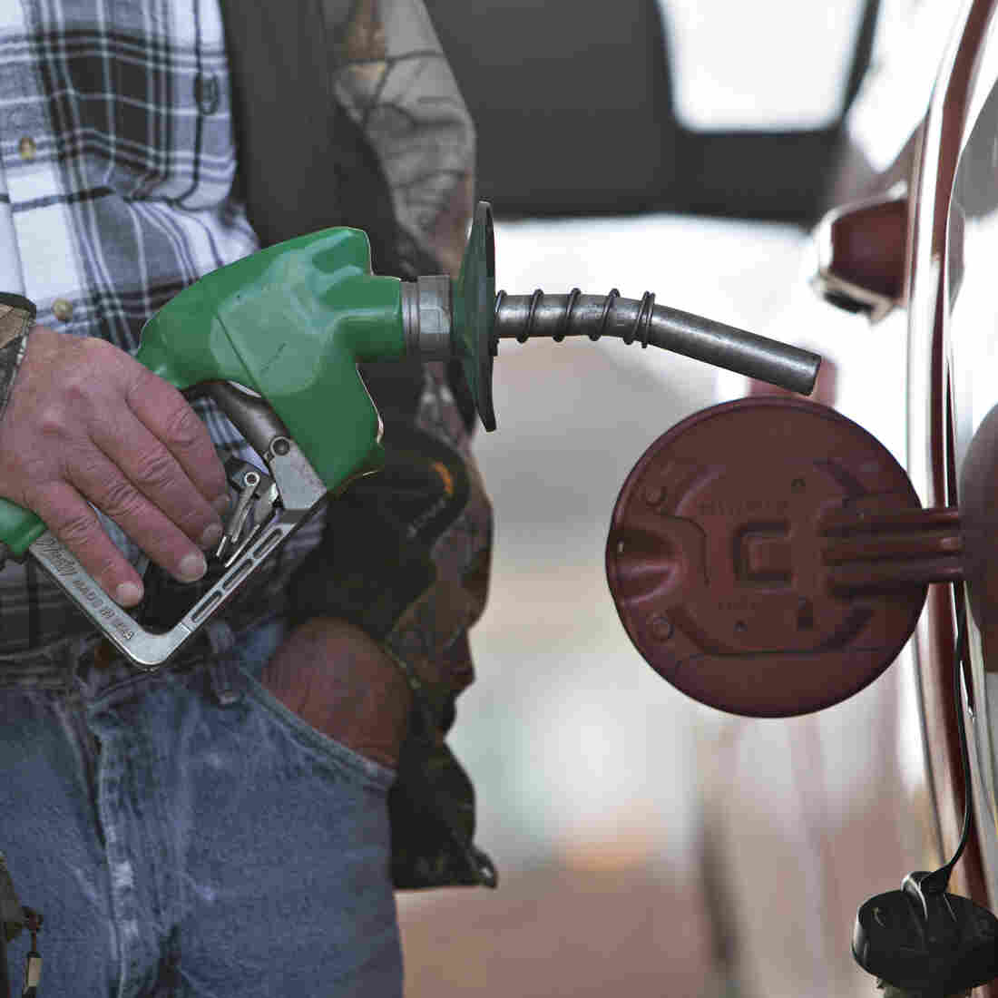 A customer fills up at a gas station in Chillicothe, Ill., in December. Low prices have meant big savings for consumers, but urban planners worry that cheap gas will encourage sprawl.