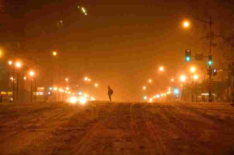 A pedestrian waits to cross a street Friday night in Washington during what may become the biggest blizzard to ever hit the area.
