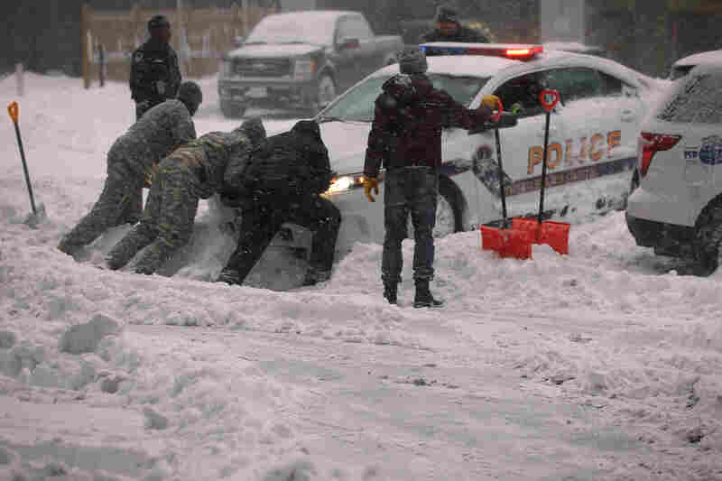 "National Guard members and other people help to push a police car that got stuck in the snow on Jan. 23 in Washington, D.C. Heavy snow continued to fall in the Mid-Atlantic region causing ""life-threatening blizzard conditions"" and affecting millions of people."