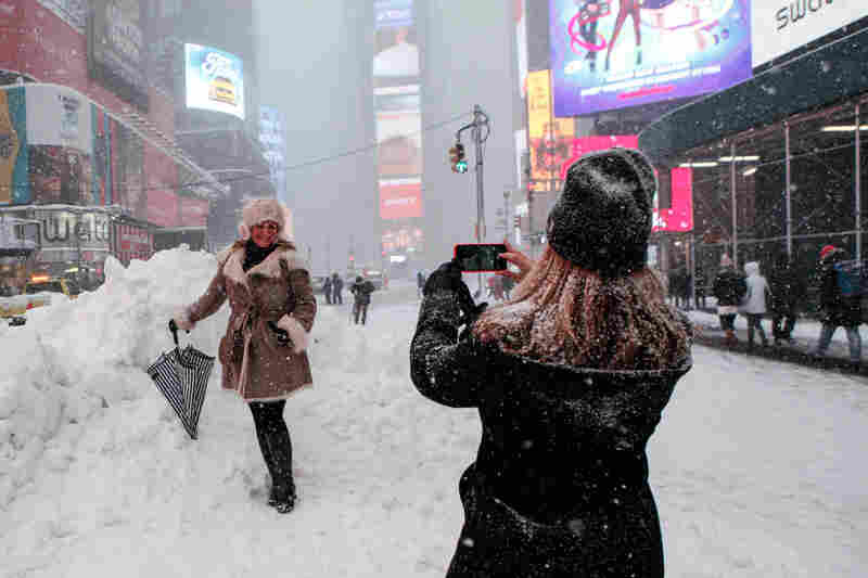 A woman poses for a picture while snow falls in New York's Times Square on Saturday.