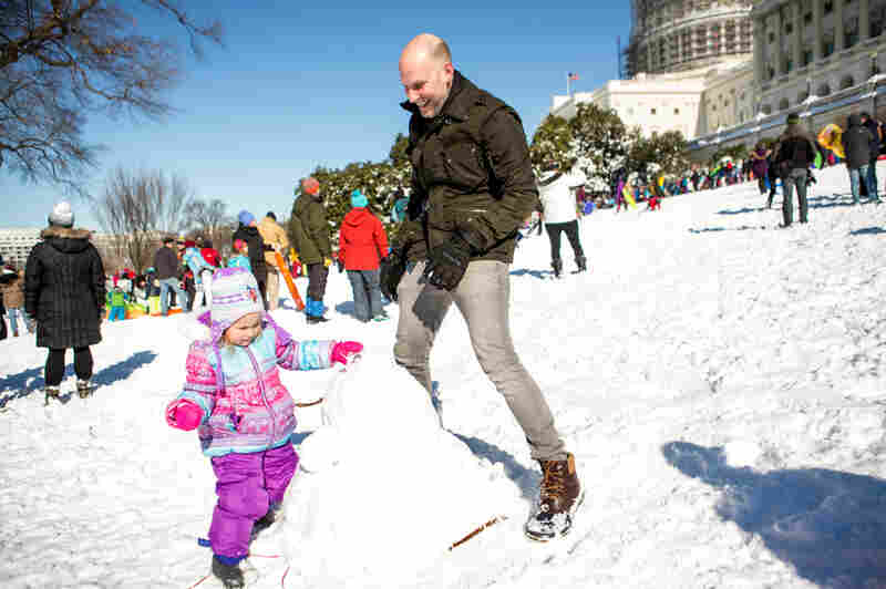 District resident Sam Carson (right) helps his daughter, Cassidy, 3, build a snowman on the Capitol lawn on Sunday.