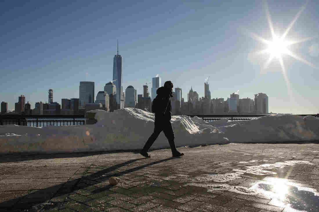 A man walks by the Hudson River Shore in Jersey City, with the New York City skyline behind him, on Sunday. A massive winter storm that lasted a day and a half finally appeared to be winding down Sunday, giving snowbound residents the chance to begin removing — and enjoying — the snow.