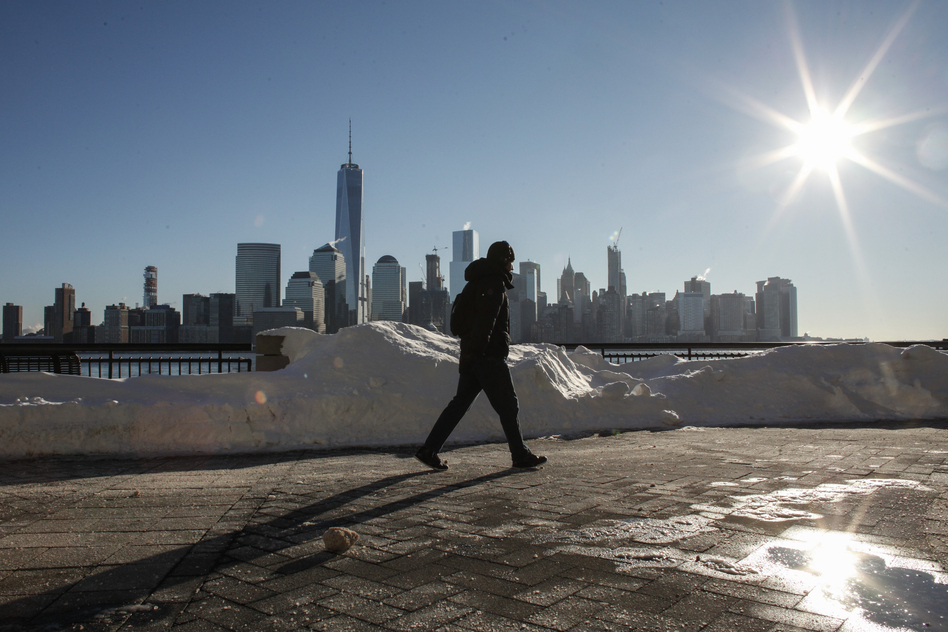 A man walks by the Hudson River Shore in Jersey City, with the New York City skyline behind him, on Sunday. A massive winter storm that lasted a day and a half finally appeared to be winding down Sunday, giving snowbound residents the chance to begin removing — and enjoying — the snow. (Kena Betancur/AFP/Getty Images)