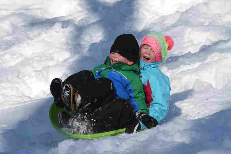 Children slide in the snow in Central Park in New York on Sunday.
