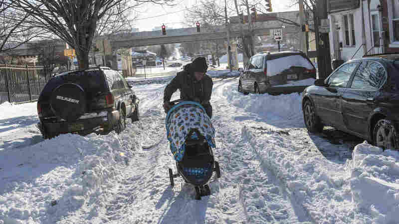 A woman pushes a stroller over a snow-covered road in Wilmington, Del., Monday. Many streets there and in other cities are still covered with snow from this weekend's blizzard.