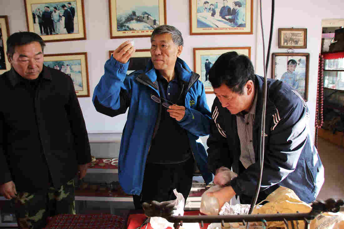 China Great Wall Society vice chairman Dong Yaohui (center) examines artifacts from the Great Wall with Xu Guohua (right), who opened a museum for these objects.