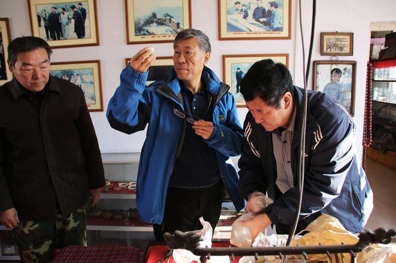 China Great Wall Society vice chairman Dong Yaohui, center, examines artifacts from the Great Wall with Xu Guohua right, who opened a museum for these objects. (Anthony Kuhn/NPR)