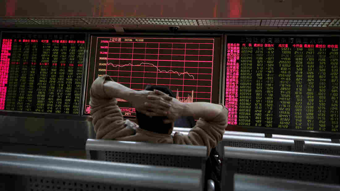 A man looks at an electronic stock board at a brokerage house in Beijing on Tuesday, a day in which Asian stock markets sank.