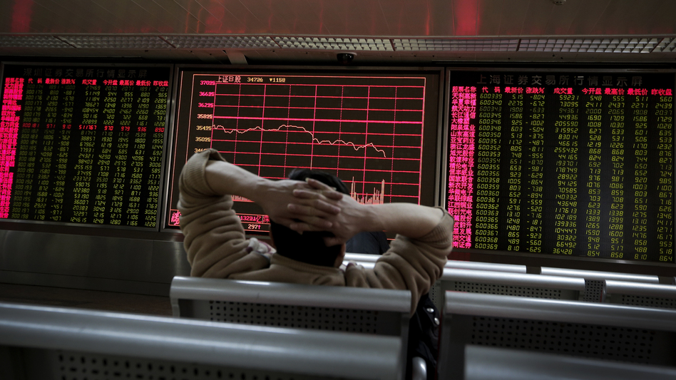 A man looks at an electronic stock board at a brokerage house in Beijing on Tuesday, a day in which Asian stock markets sank. (Andy Wong/AP)