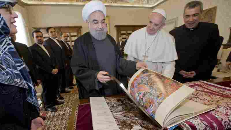 Iranian President Hassan Rouhani opens a book he gave to Pope Francis as a gift at the Vatican on Tuesday. Rouhani is the first Iranian leader to meet with the pope since 1999. With sanctions against Iran falling away, Rouhani also announced business agreements with Italy as part of his visit to Europe.