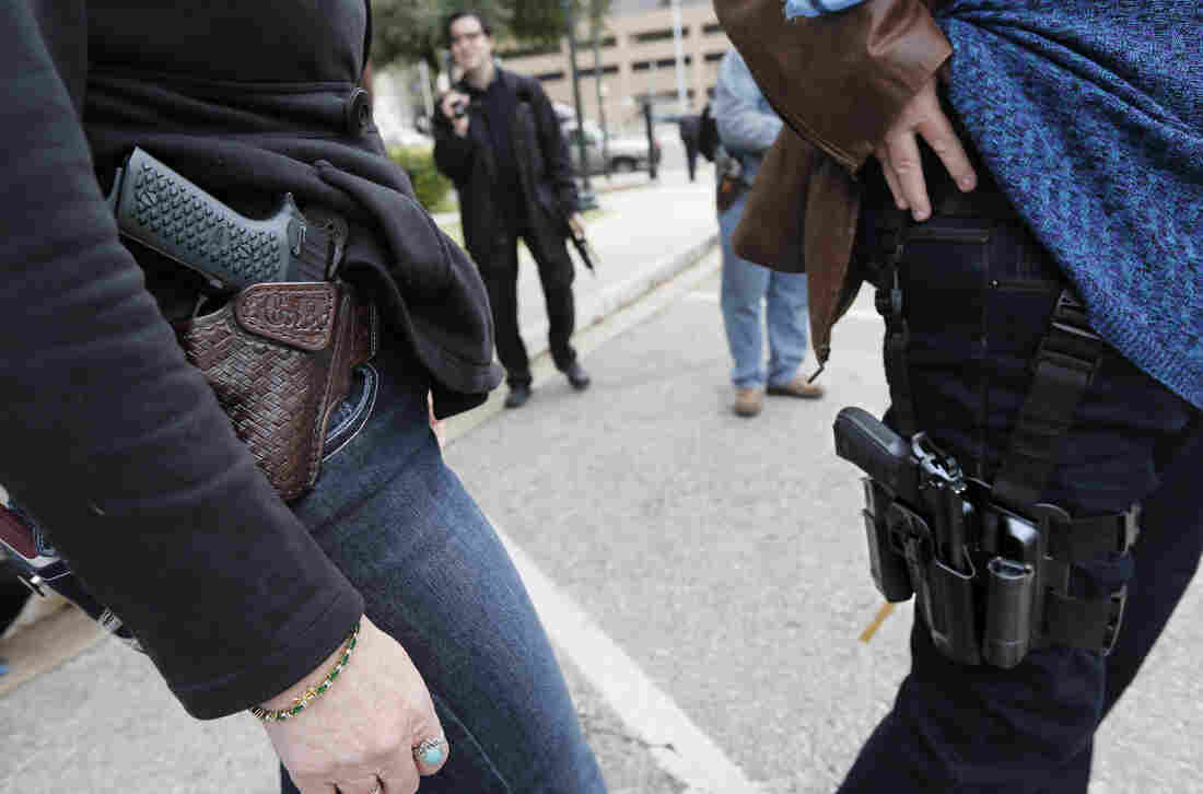 Two women compare handgun holsters during an open-carry rally at the Texas State Capitol in Austin on Jan. 1.