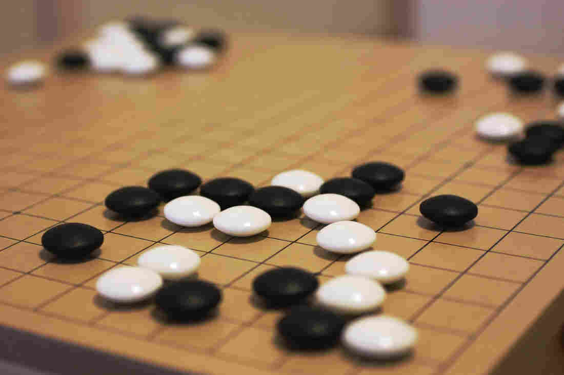 In the game Go, players use white or black stones to attempt to fence off territory.