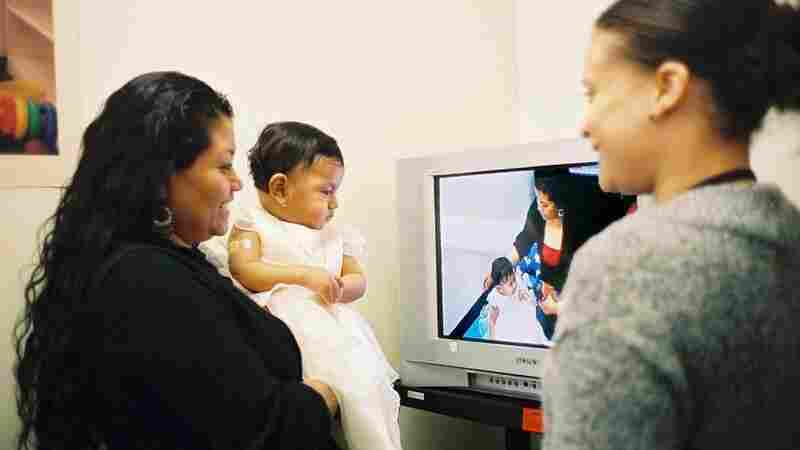 A mother watches a video taken of herself playing with her daughter while at Bellevue Hospital in New York for a checkup. Brenda Woodford provides coaching on parenting skills.