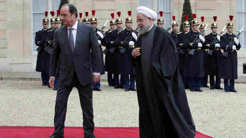 French President Francois Hollande (left) greets Iranian President Hassan Rouhani before a meeting at the Elysee Palace in Paris on Thursday. Rouhani's visit to Europe this week has been accompanied by numerous business deals announced by Iran and European companies. Peugeot-Citroen said Thursday it was returning to Iran to build cars with an Iranian automaker.