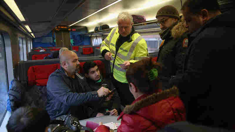 A Danish policeman checks passengers' identity papers on a train arriving from Germany on Jan. 6. Officials say the small country is overwhelmed by the number of refugees seeking asylum.