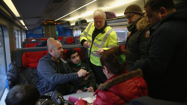 A Danish policeman checks passengers' identity papers on a train arriving from Germany on Jan. 6. Officials say the small country is overwhelmed by the number of refugees seeking asylum. (Getty Images)