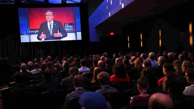 Republican presidential candidate Jeb Bush is seen on a TV screen as he participates in Thursday's debate in Des Moines, Iowa.