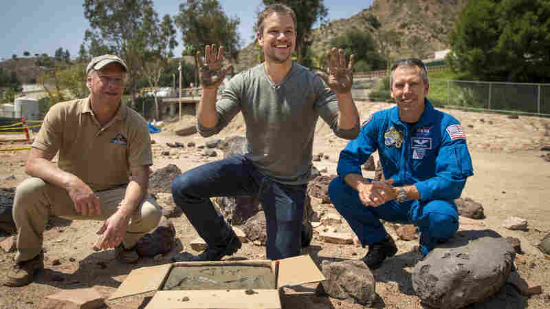 Actor Matt Damon, who stars as NASA Astronaut Mark Watney in the film The Martian, center, makes hand prints in cement at the Jet Propulsion Laboratory (JPL) Mars Yard in Pasadena, Calif. in Aug. 2015. Damon is shown with Mars Science Lab Project Manager Jim Erickson, left, and NASA Astronaut Drew Feustel.