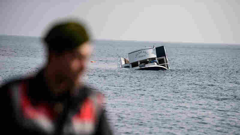 A sinking boat is seen behind a Turkish gendarme off the coast of Canakkale's Bademli district on Saturday. At least 35 migrants drowned when their boat sank in the Aegean Sea while trying to cross from Turkey to Greece.