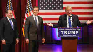 Donald Trump (right) brings the two most recent Iowa winners, Mike Huckabee (left) and Rick Santorum, on stage during Trump's rally for veterans, an event he held instead of attending the GOP debate.