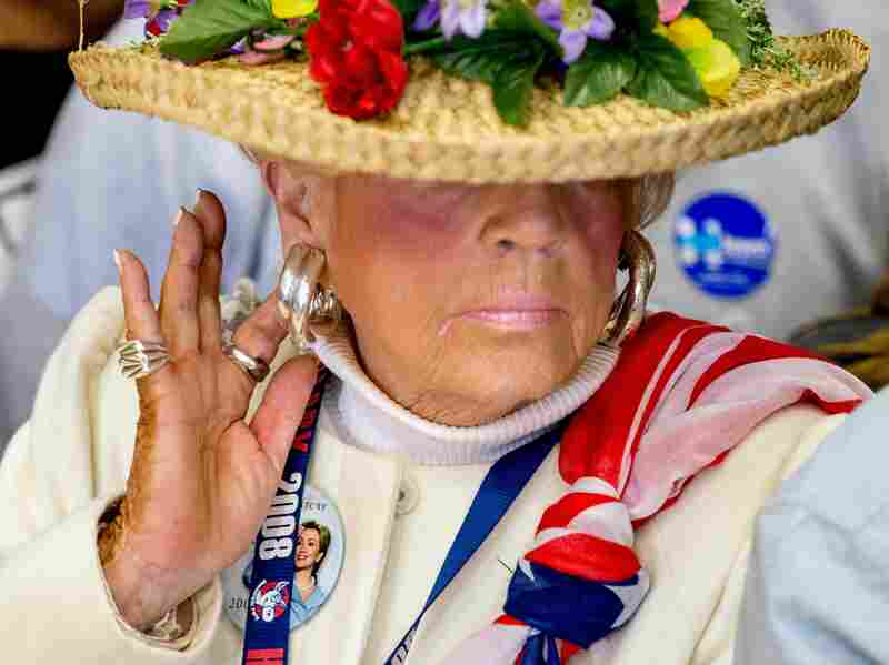 A woman at a Clinton event wears a campaign button as she stands in the audience during a rally for the candidate.