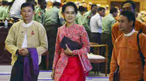 Myanmar's Aung San Suu Kyi (center) walks along with other lawmakers of her National League for Democracy party after a regular session of the lower house of parliament Monday.